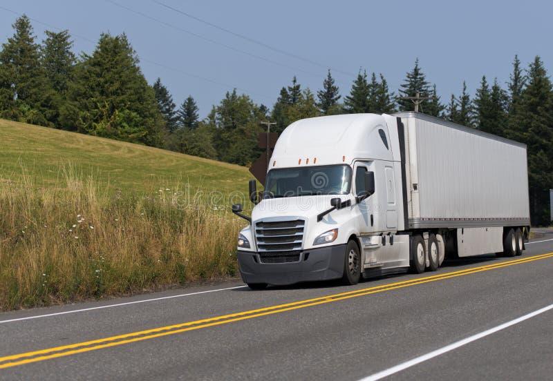 White big rig semi truck transporting dry van semi trailer on th. White modern bonnet professional technological big rig semi truck transporting dry van semi stock photography
