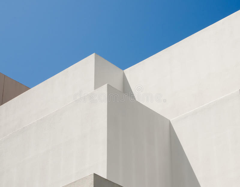 White Modern Building, Blue Sky. A abstract design is formed by the clean white and grey patterns of the walls of a modern building against a strong blue sky royalty free stock image