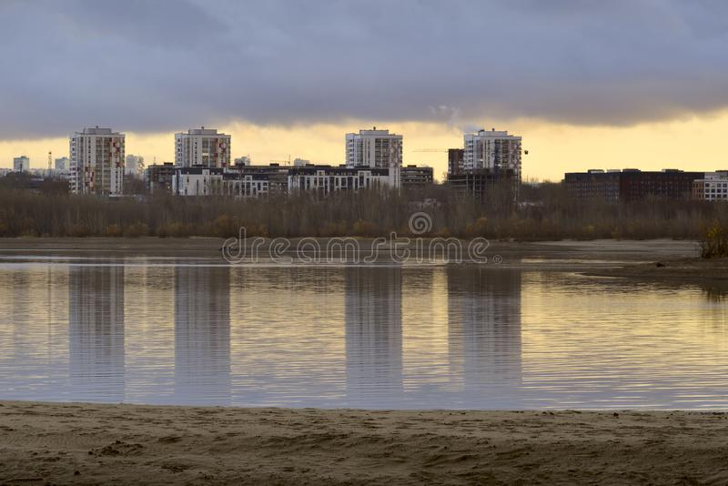 Houses on the autumn bank of the Ob River in Novosibirsk. White modern homes. Autumn sandy bank of the Ob River. Reflections in the water. Yellow sky on the stock image