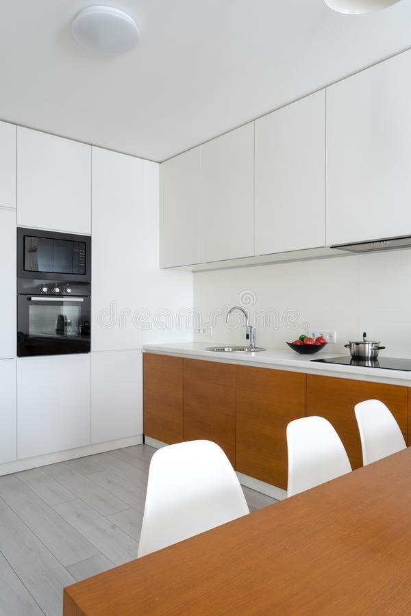 White modern kitchen room with modern interior in cozy flat royalty free stock photos