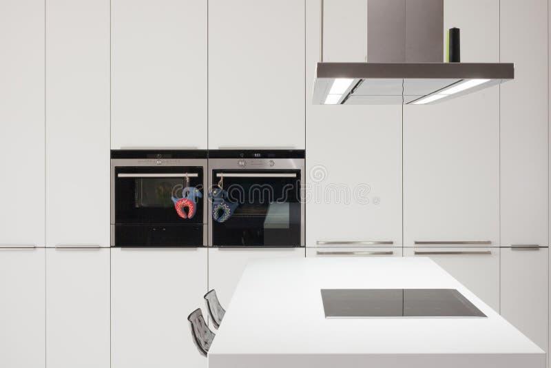 White modern kitchen with steel appliances. White modern kitchen with steel appliances stock image