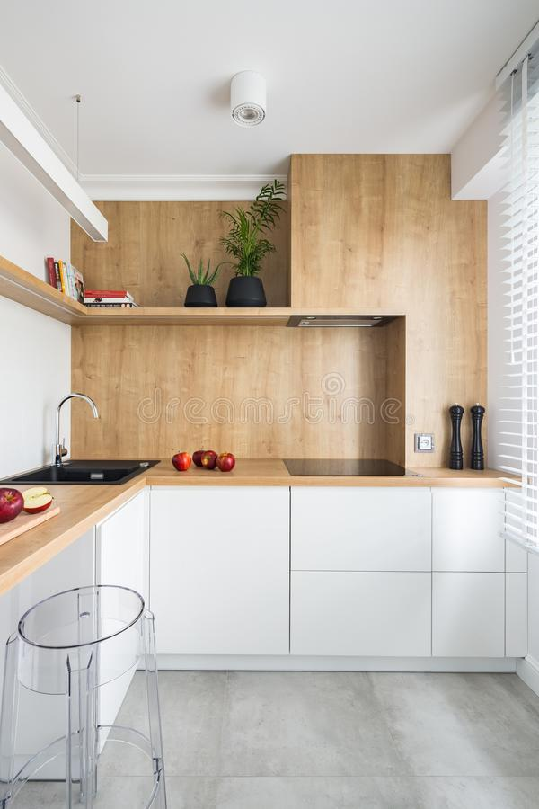 White kitchen with wooden furniture stock photography