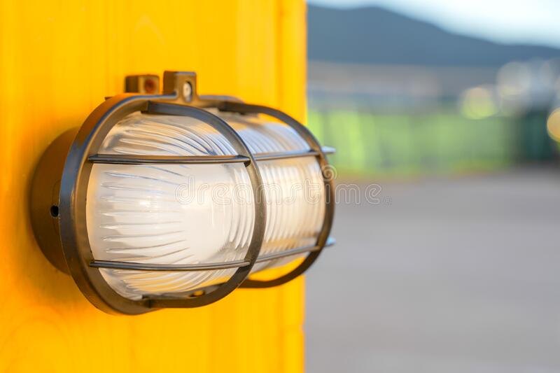 White modern lamp lantern on a yellow wall in a street parking.  stock images