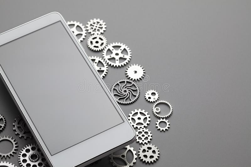 White modern mobile phone with blank gray screen and small gears on table royalty free stock images