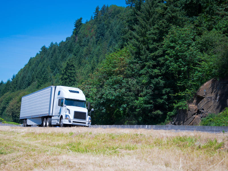 White modern semi truck reefer trailer on green summer highway. Modern semi truck with a high cabin and the refrigeration unit on the reefer trailer with spoiler royalty free stock image