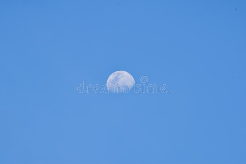 White moon in the blue sky before sunset. The moon rose at Early Evening afternoon air astrology astronomy background beautiful beauty bright celestial close royalty free stock photos