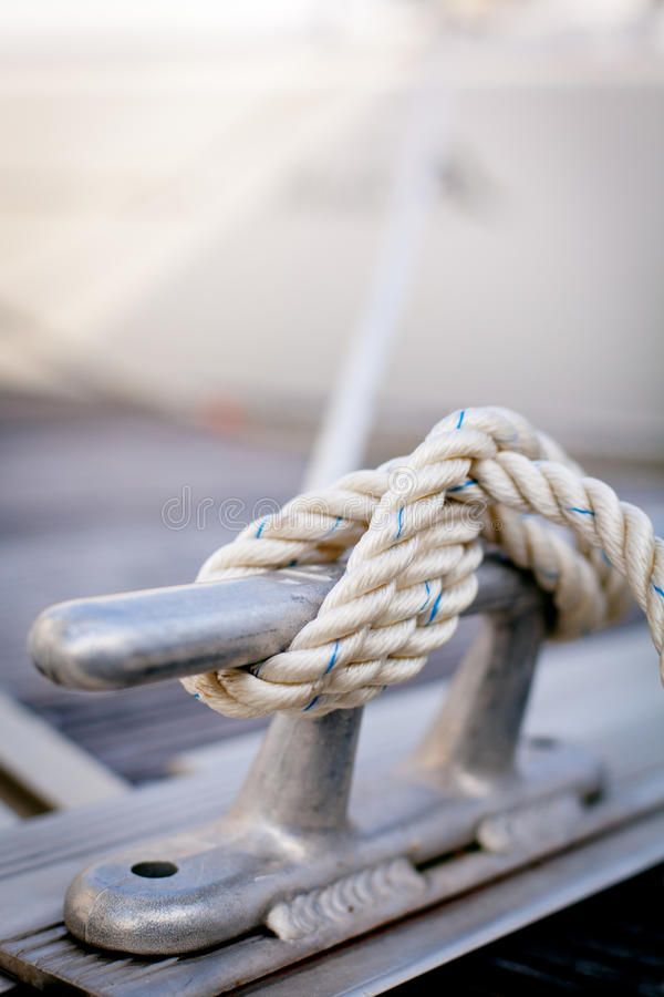 White mooring rope on ship. Closeup of white mooring rope tied around steel anchor on boat or ship stock photography