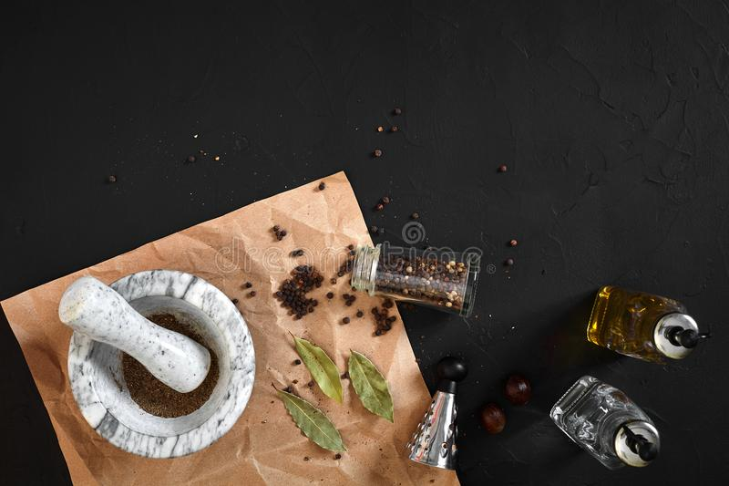 White mortar and pestle with dried peppers in flat lay on black background royalty free stock photos