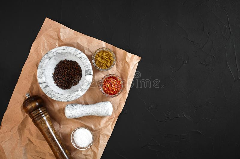White mortar and pestle with dried peppers in flat lay on black background royalty free stock photography