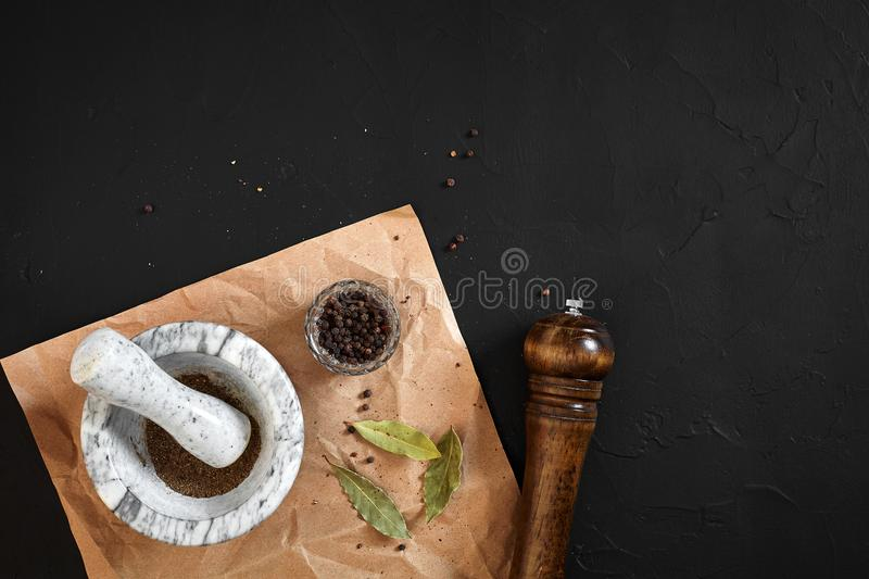 White mortar and pestle with dried peppers in flat lay on black background. Copy space. Still life. Top view royalty free stock images