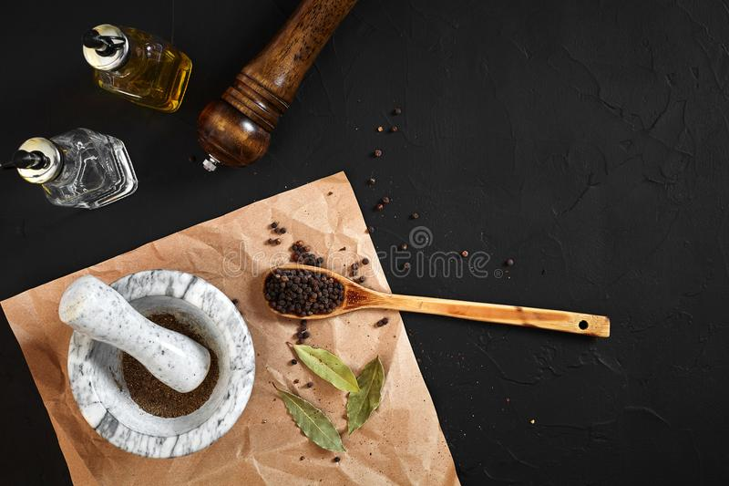 White mortar and pestle with dried peppers in flat lay on black background stock photos