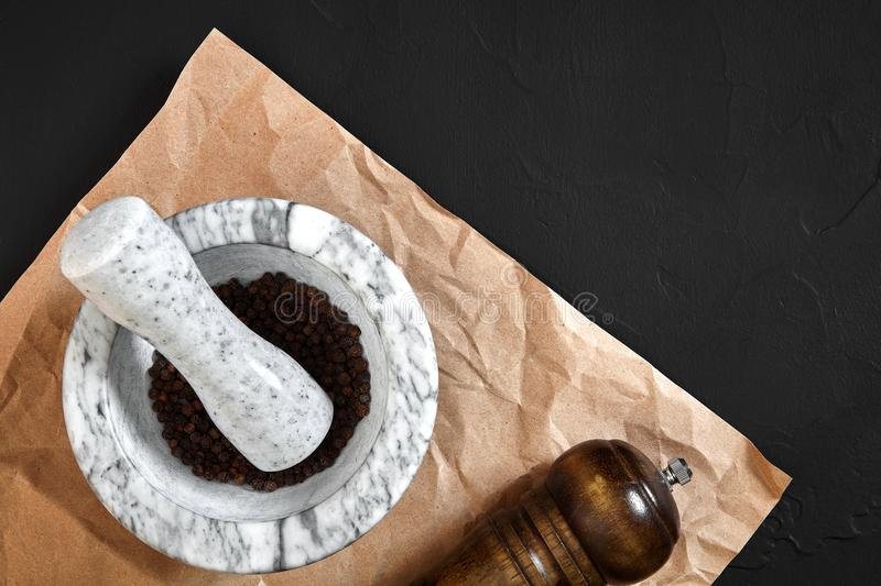 White mortar and pestle with dried peppers in flat lay on black background royalty free stock photo