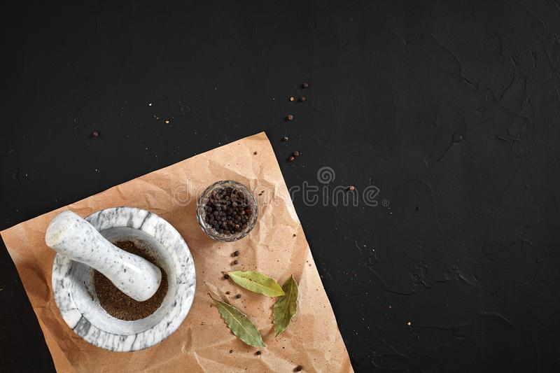 White mortar and pestle with dried peppers in flat lay on black background royalty free stock image