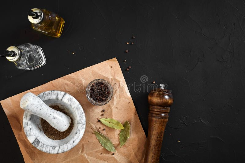 White mortar and pestle with dried peppers in flat lay on black background stock image