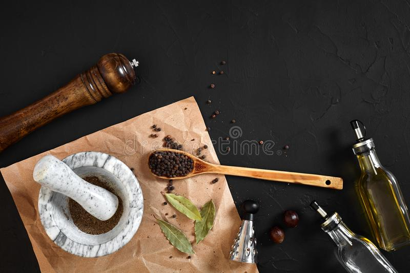 White mortar and pestle with dried peppers in flat lay on black background royalty free stock images