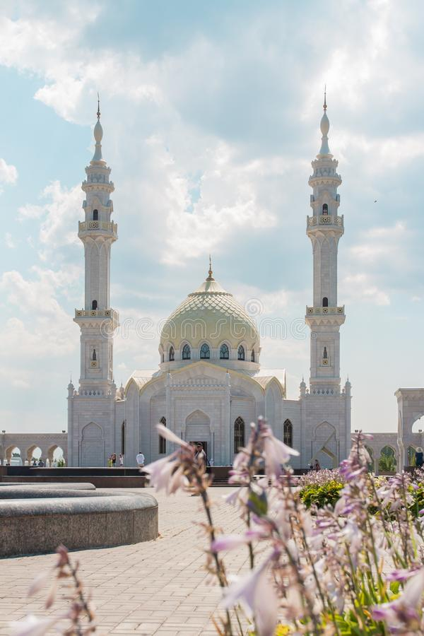 The white mosque against the sky and flowers. stock photo