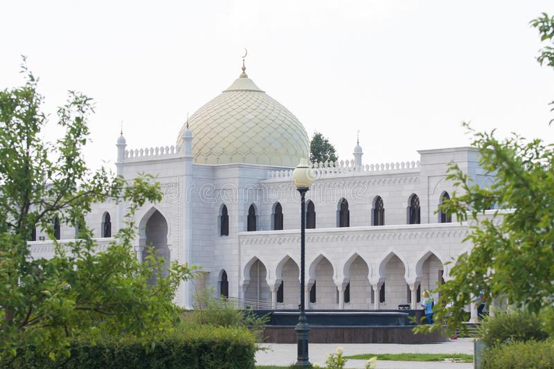 White mosque building with yellow dome and beautiful arches. stock photos