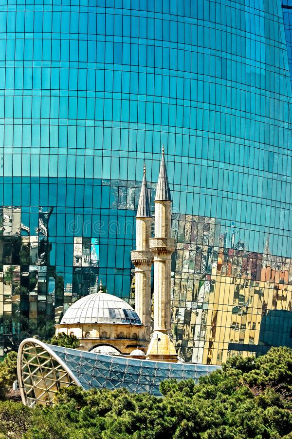 White mosque with a high minaret reflected in the glass surface of a modern skyscraper in Baku, Azerbaijan.  royalty free stock image