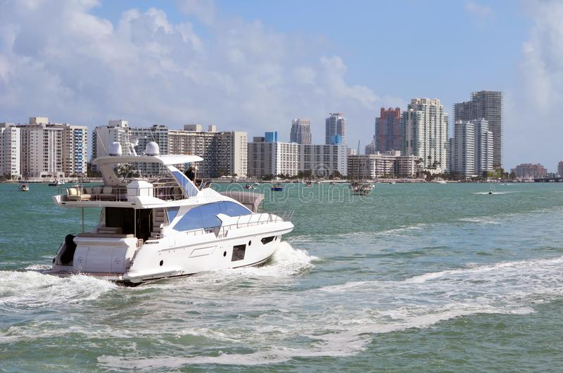 White Motor Yacht and Southbeach Skyline. A small luxury white motor yacht cruising on the intra-coastal waterway off Miami Beach,Florida with Miami Beach condo stock photography