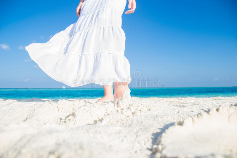 White moving skirt and feet on the tropical beach stock images