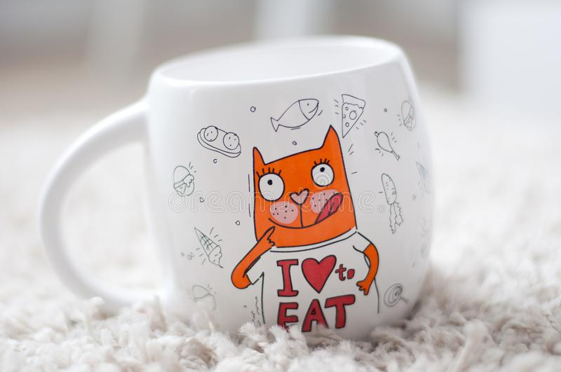 A white mug, a big, a mug with tea, a mug with coffee, bright picture, funny cat royalty free stock photos