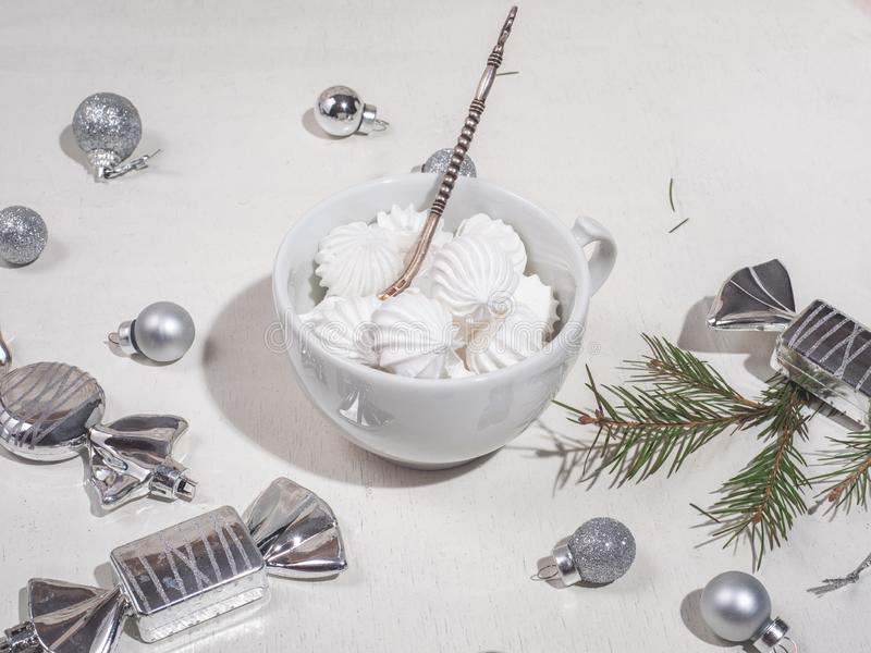 White mug with bisa biscuit, silver teaspoon in bright colors. Christmas toys and a sprig of spruce on a white table royalty free stock images