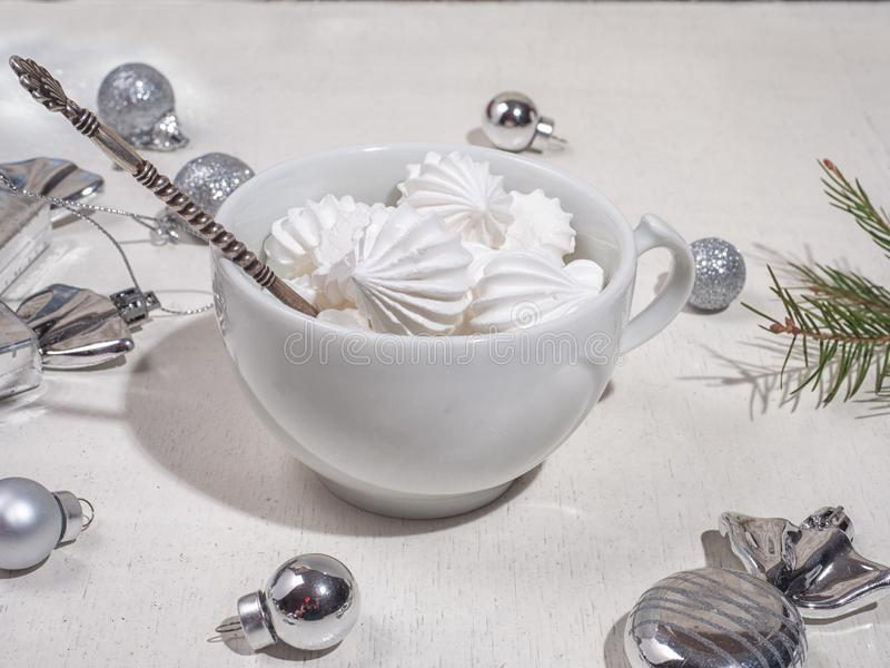 White mug with biscuit biscuits and silver teaspoon in light colors. White mug with biscuit biscuits and silver teaspoon in bright colors with Christmas stock photo
