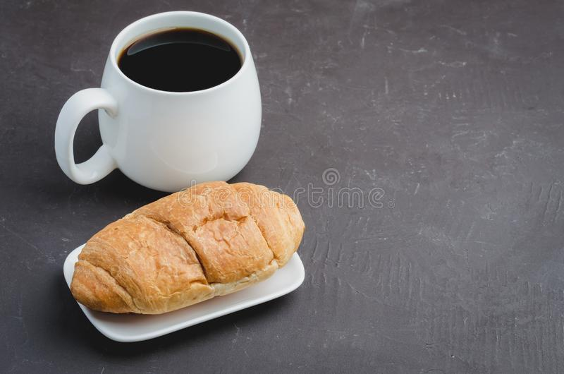 White mug with black coffee and croissant on dark stone background with copyspace.  Coffee break stock image