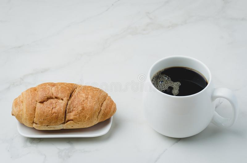 White mug with black coffee and croissant on white stone table. Coffee break royalty free stock images