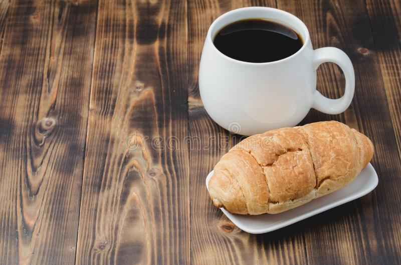 White mug with black coffee and croissant on wooden background with copyspace. Coffee break stock photo