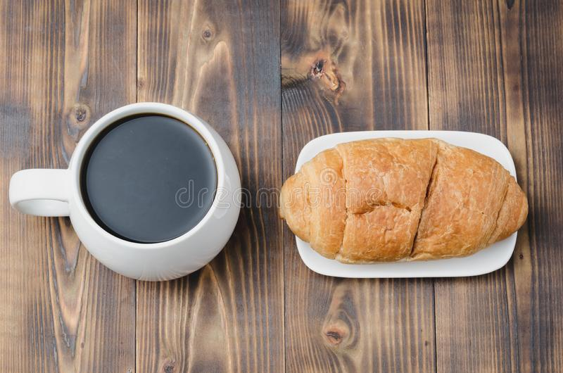 White mug with black coffee and croissant on wooden background. Top view. Coffee break royalty free stock images