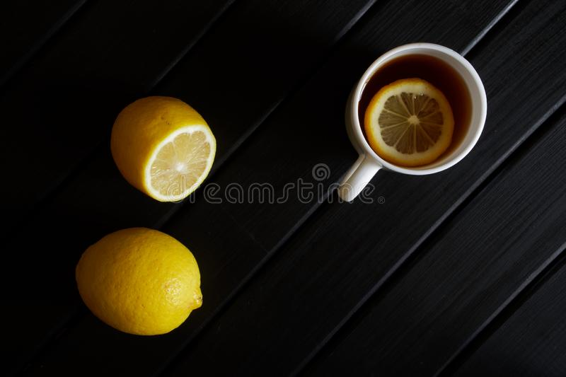 A white mug with black tea and a slice of lemon stands next to the fruit on a dark wooden surface. View from above. Minimalism stock image