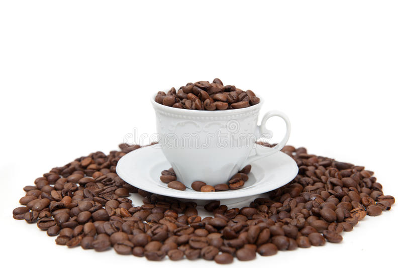 The white mug with coffee beans royalty free stock image