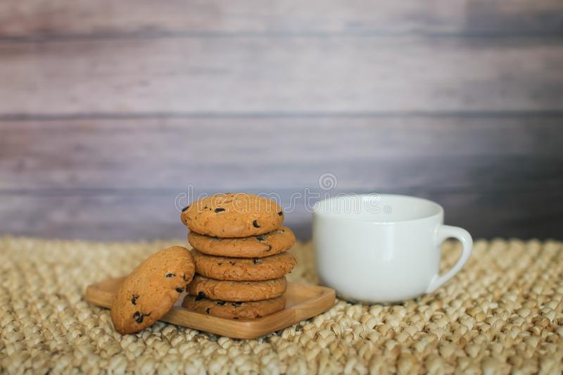 White mug and homemade oatmeal cookies folded in a pile on wooden plate and wooden background royalty free stock image