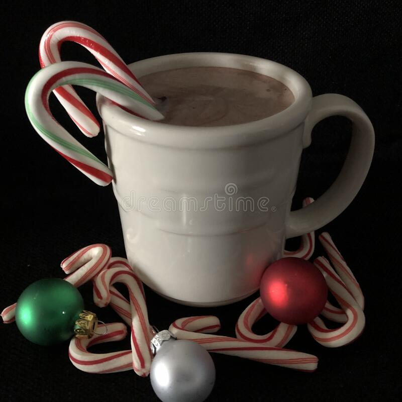 Mug of Hot Chocolate with Candy Canes. White mug with hot chocolate, candy canes and Christmas bulbs stock images