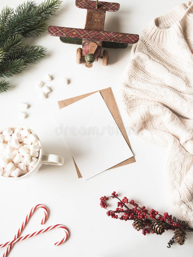 White mug with hot drink and marshmallows, paper card for letter, envelope,knitted plaid and xmas decoration on white background. stock images