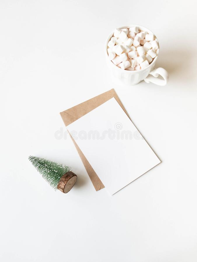 White mug with hot drink and marshmallows, paper card for letter, envelope and small Christmas tree on white background. Top view stock image