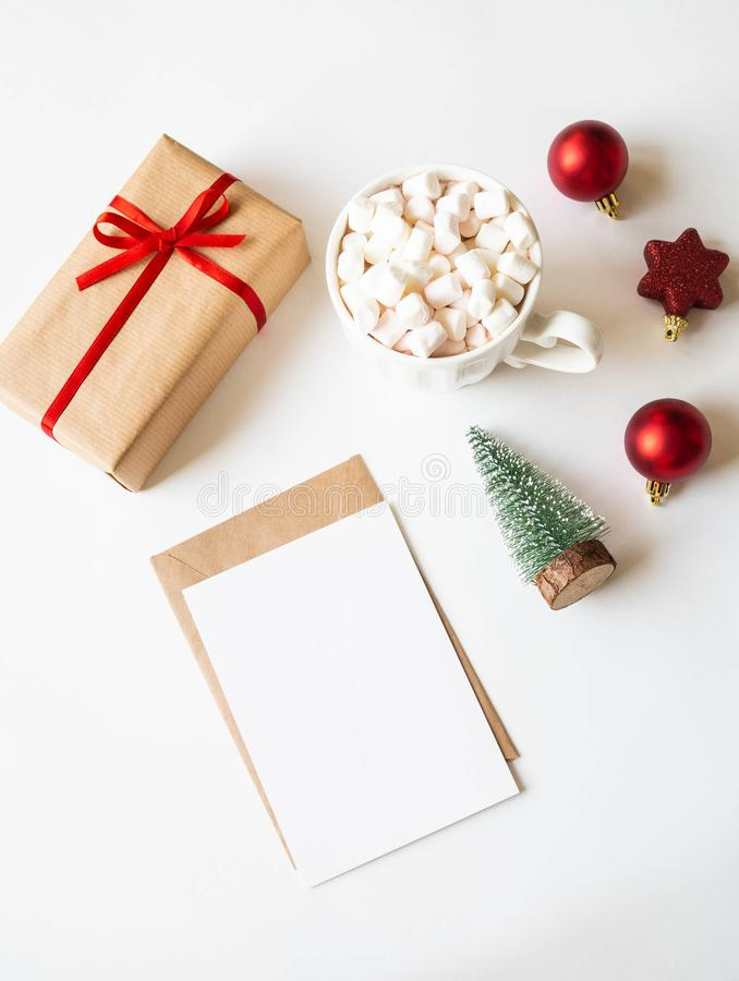 White mug with hot drink and marshmallows, paper card for letter, envelope and xmas decoration on white background. Top view. Copy royalty free stock photography