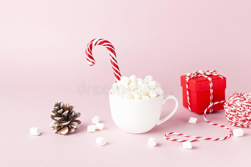 White mug with marshmallows Candy Cane, red gift box, pine cone, decorative lace on pink background Flat Lay Winter traditional stock photos