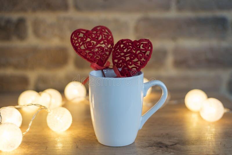 White Mug Mock Up with Two Red Hearts Valentine Day Concept Achtergrond en lichten voor brick royalty-vrije stock afbeelding