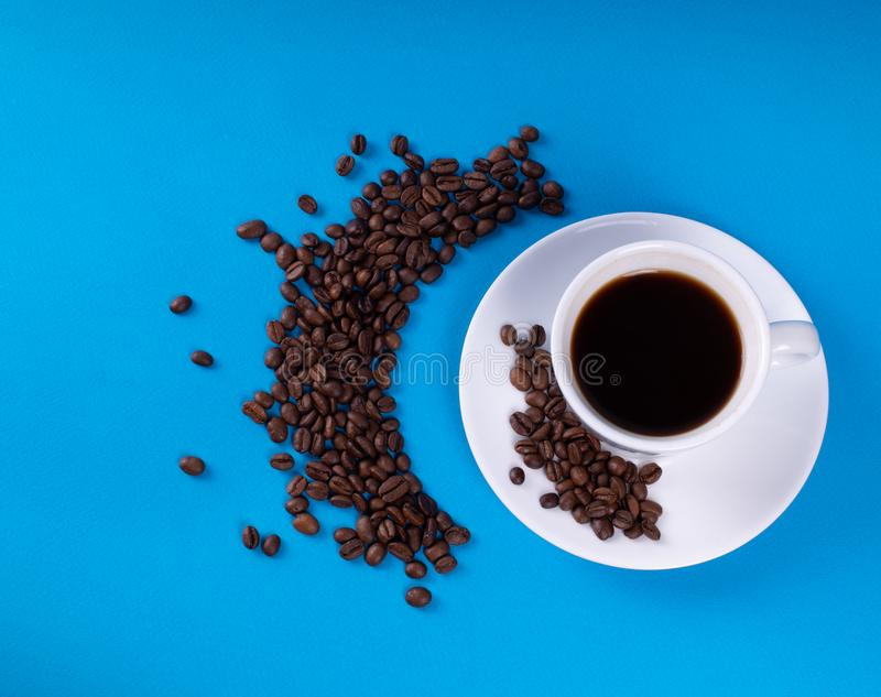 A white mug on a saucer with a black drink is set on a blue background with a number of scattered crescent coffee grains stock image