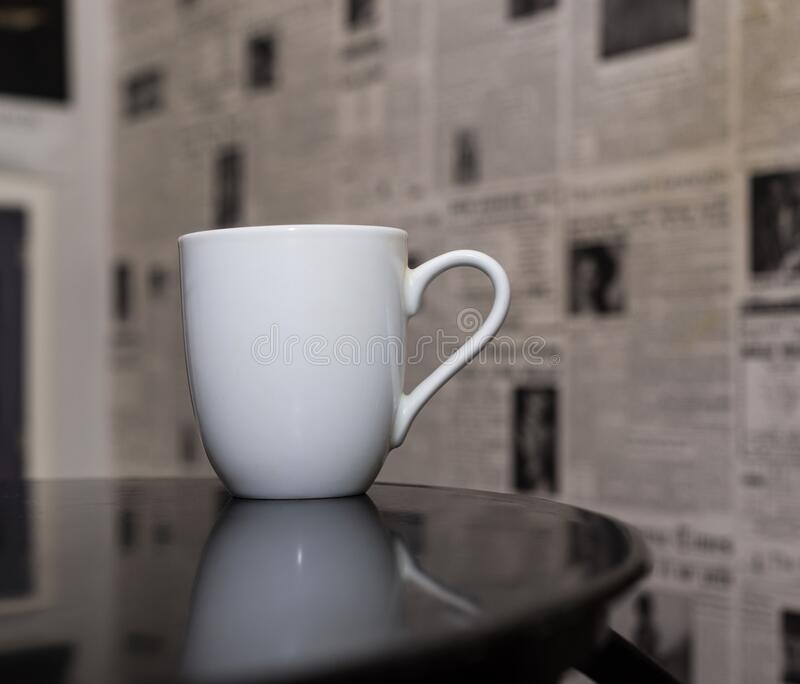 White mug on table. With newspaper wallpaper background stock images
