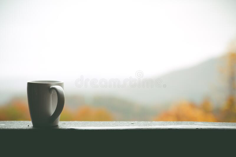 White Mug on Window over Looking Autumn Trees and Hills in Distance during Daytime royalty free stock photography