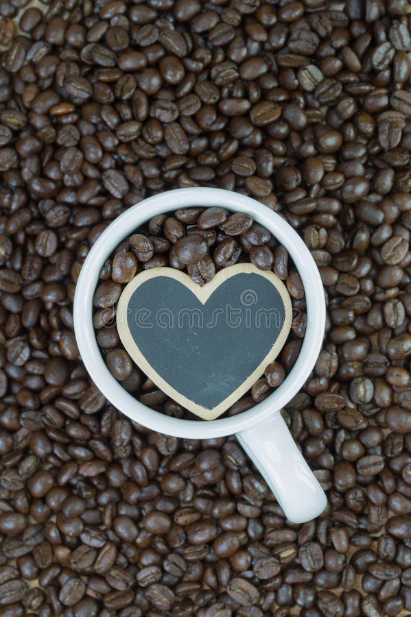 White mug and wooden heart shape on coffee beans background royalty free stock photography