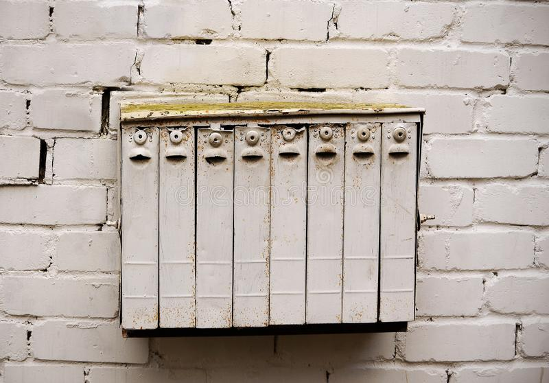 White multi devision mailbox hanging on white brick wall royalty free stock images