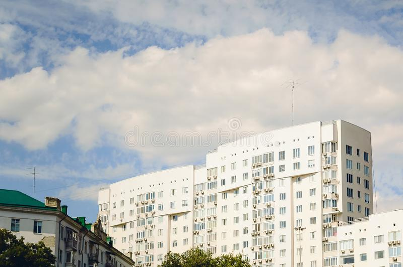 A white multi-storey residential building against the blue sky. Beautiful view royalty free stock images
