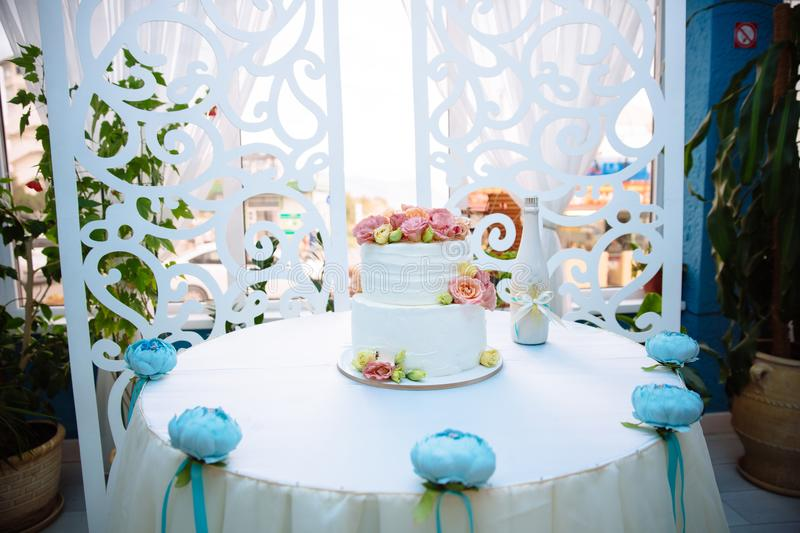 White multilevel wedding cake decorated with pink cream flowers on white table. Candy bar concept.  stock photos