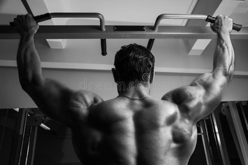 White Muscular fitness model hanging on the chin-up bar, showing his back BW royalty free stock images