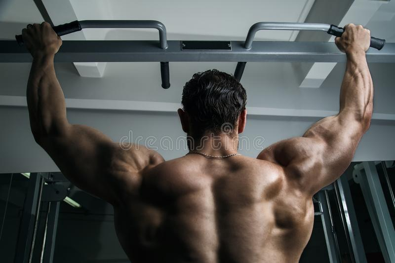 White Muscular man fitness model hanging on the chin-up bar, showing his back royalty free stock photos