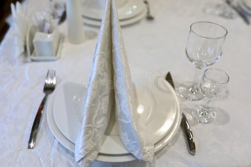 White napkin in form of sail. In restaurant royalty free stock photo